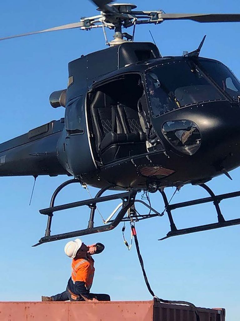 Helicopter hovering over engineer at Jan Juc Beach access steps installation