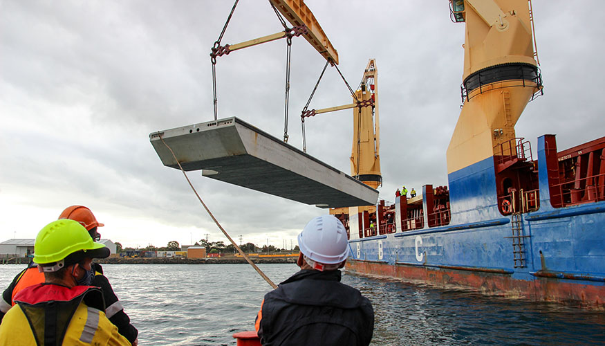 Wave attenuator being unloaded from vessel